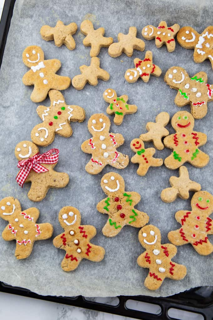 Vegan Gingerbread Cookies decorated with icing on a baking sheet lined with parchment paper