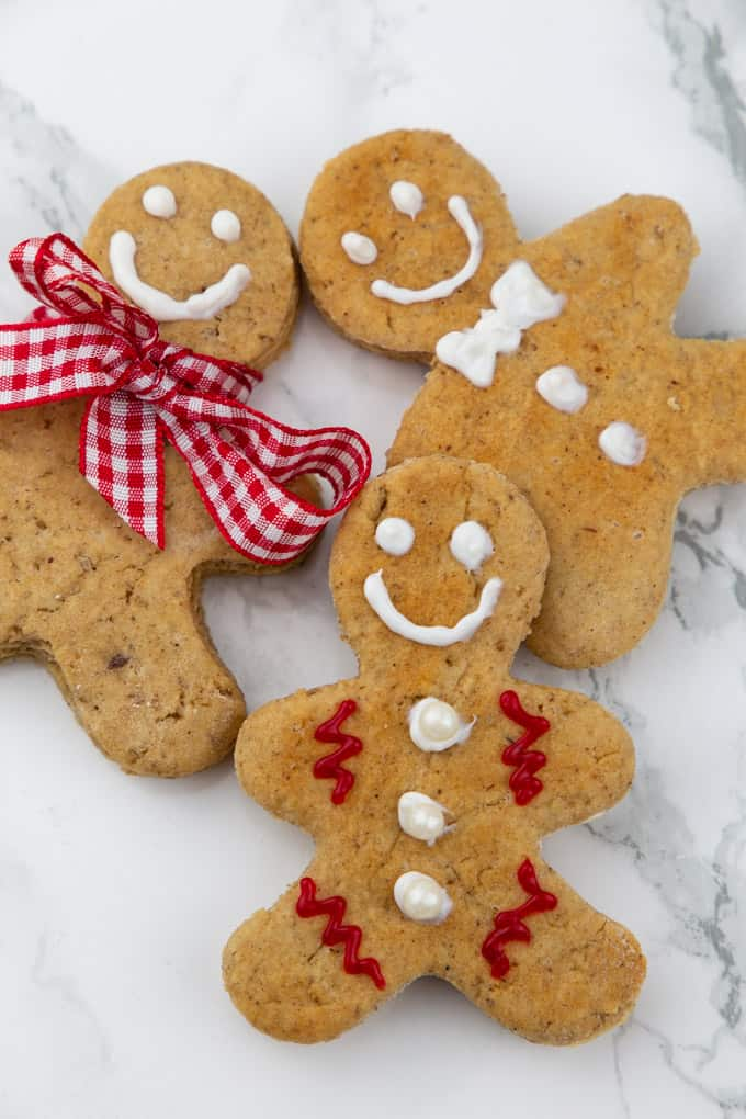 three vegan gingerbread men decorated with icing and a red ribbon on a marble countertop