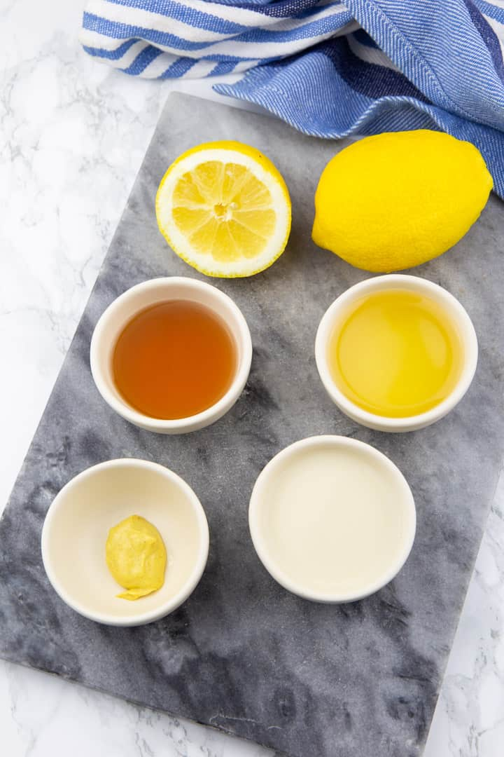 four little bowls with apple cider vinegar, oil, soy milk, and mustard on a marble cutting board with two lemons on the side