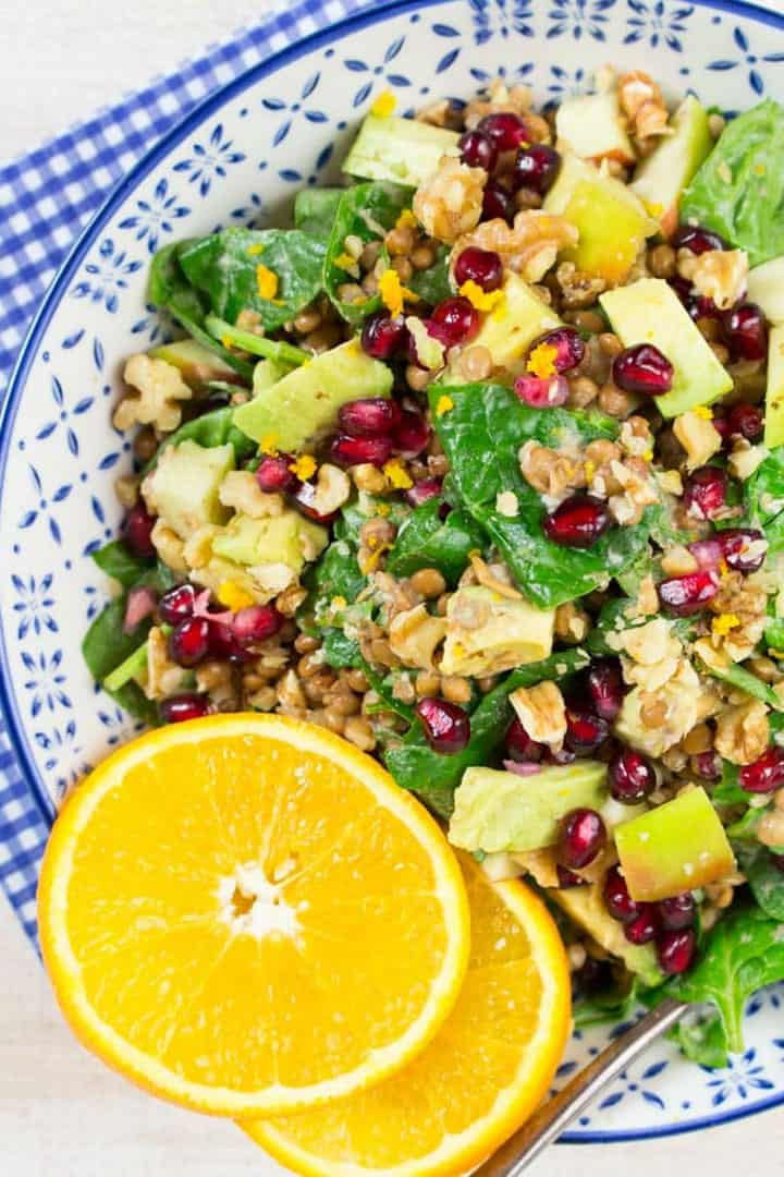 lentil salad with spinach and pomegranate in a white and blue bowl with two orange slices on top