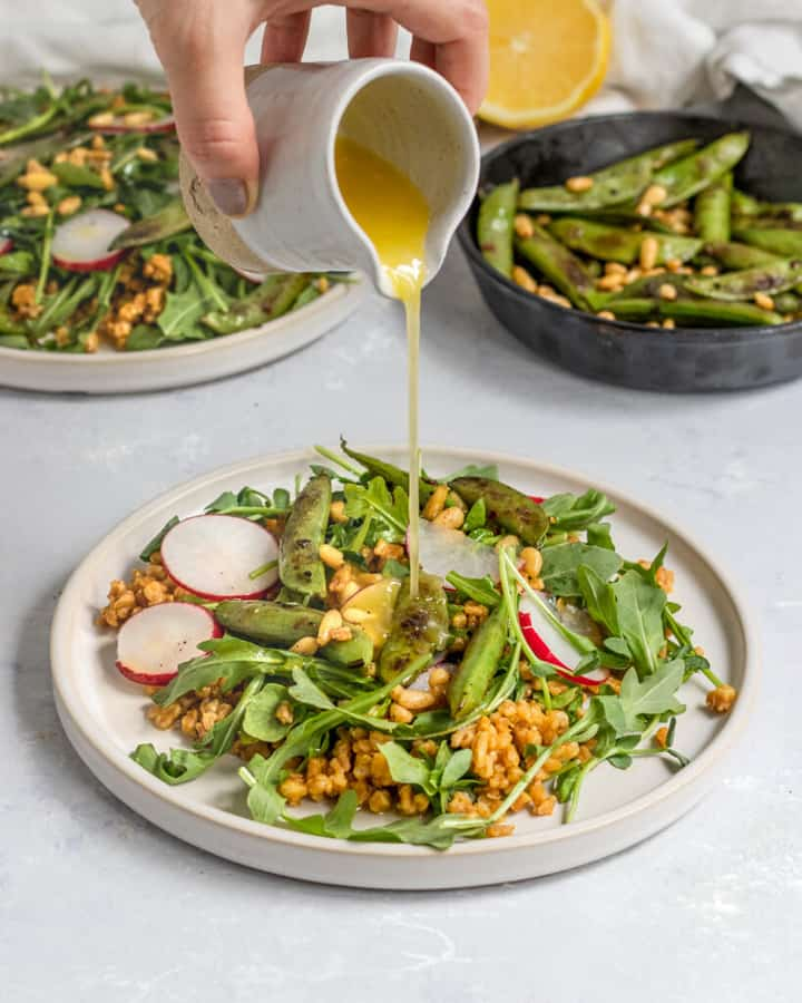 Vegan Snap Pea Arugula Farro Salad on two white plates with a hand pouring the dressing over the salad