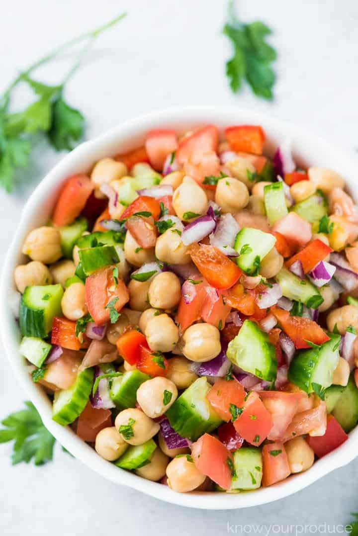 Chickpea Salad with tomatoes and cucumbers in a white bowl on a white countertop with fresh parsley on the side