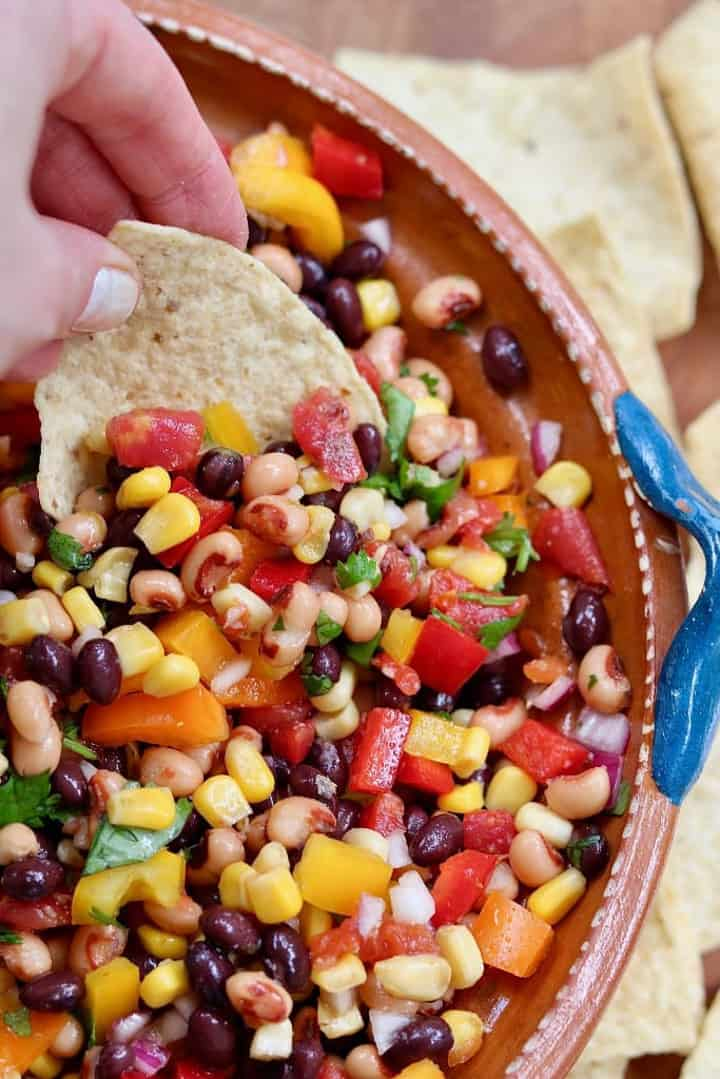 Cowboy Caviar with nacho chips on the side and a hand dipping a nacho into the salad