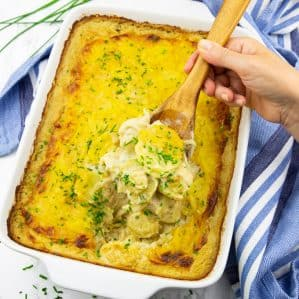 Vegan Scalloped Potatoes in a white baking dish with a hand holding a wooden spoon with scalloped potatoes