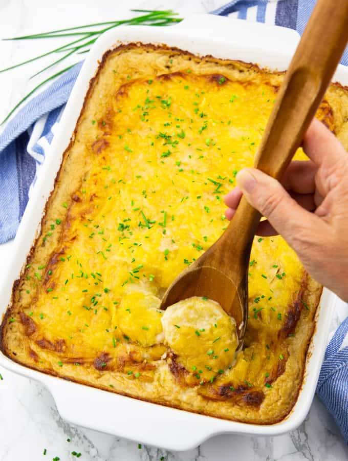 scalloped potatoes in a white baking dish on a marble countertop with a hand holding a wooden spoon