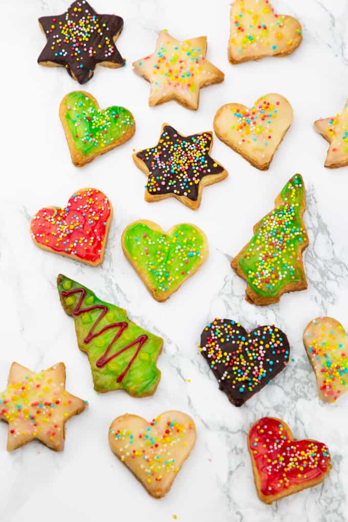 Decorated vegan sugar cookies in heart, star, and Christmas tree shape on a marble countertop