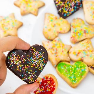 a hand holding a vegan sugar cookie covered in chocolate and sprinkles with more cookies on a white plate in the background