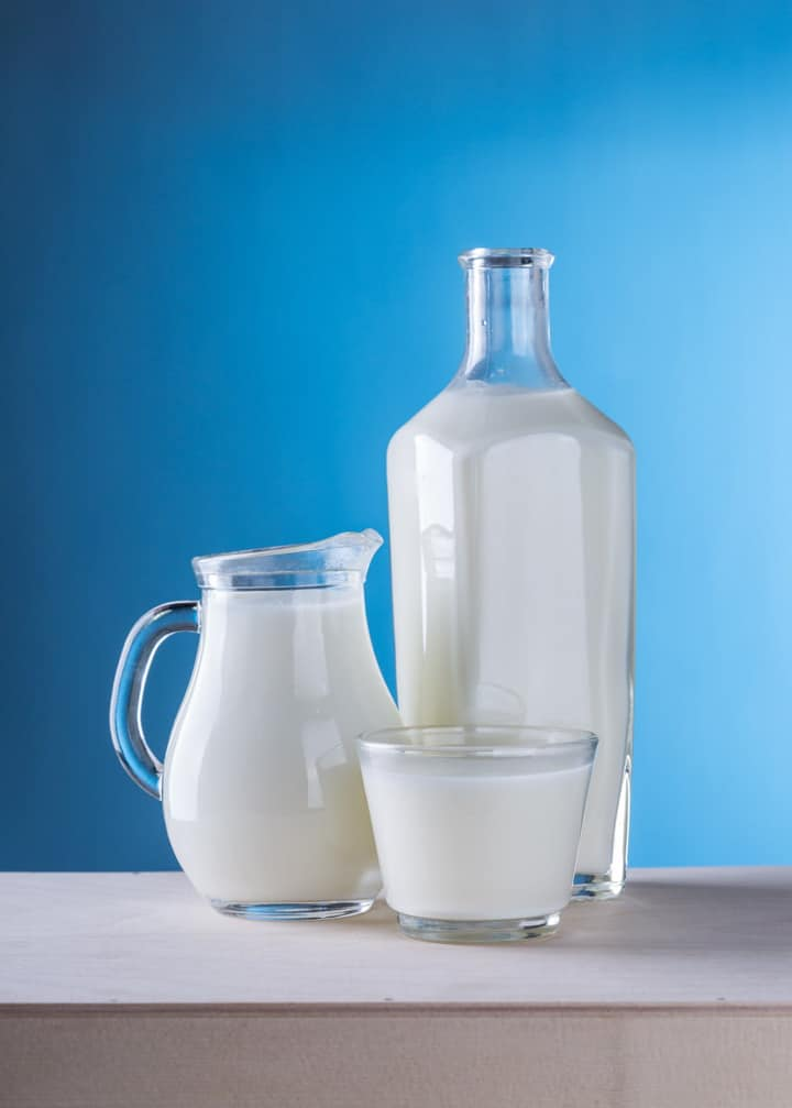 a glass, a bottle, and a milch pitcher with a blue background
