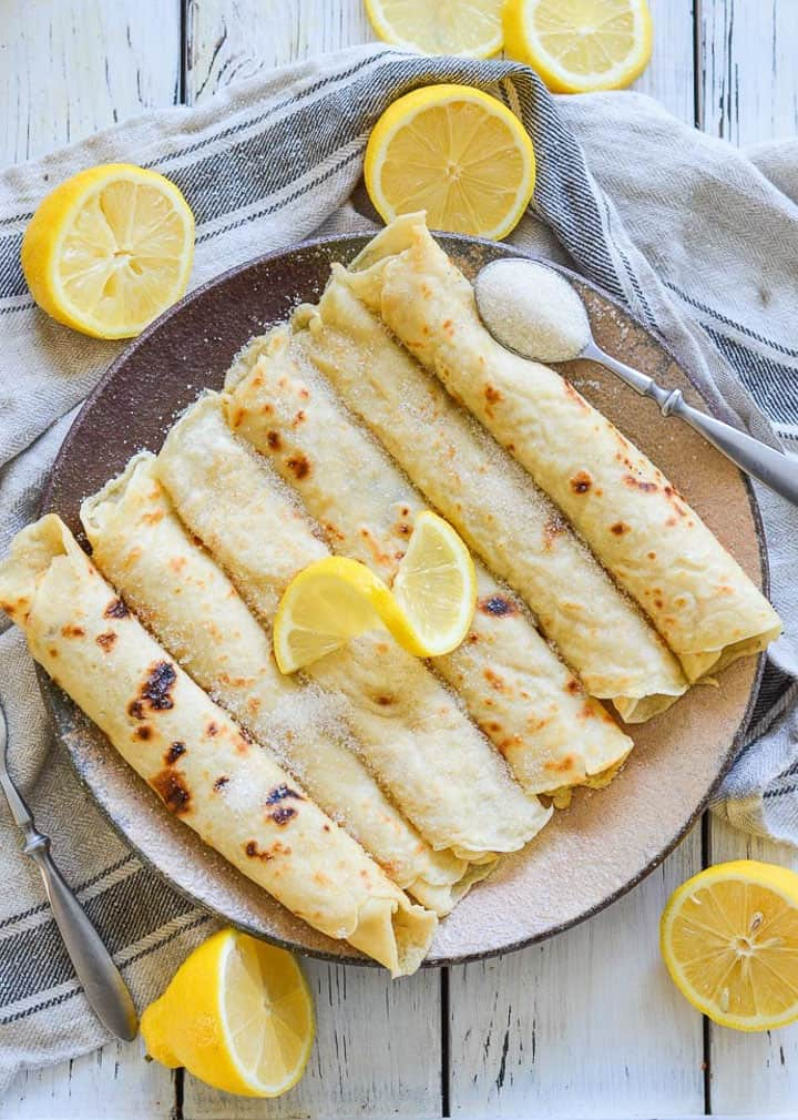 six English vegan pancakes rolled up on a white plate with lemon slices on top and on the side