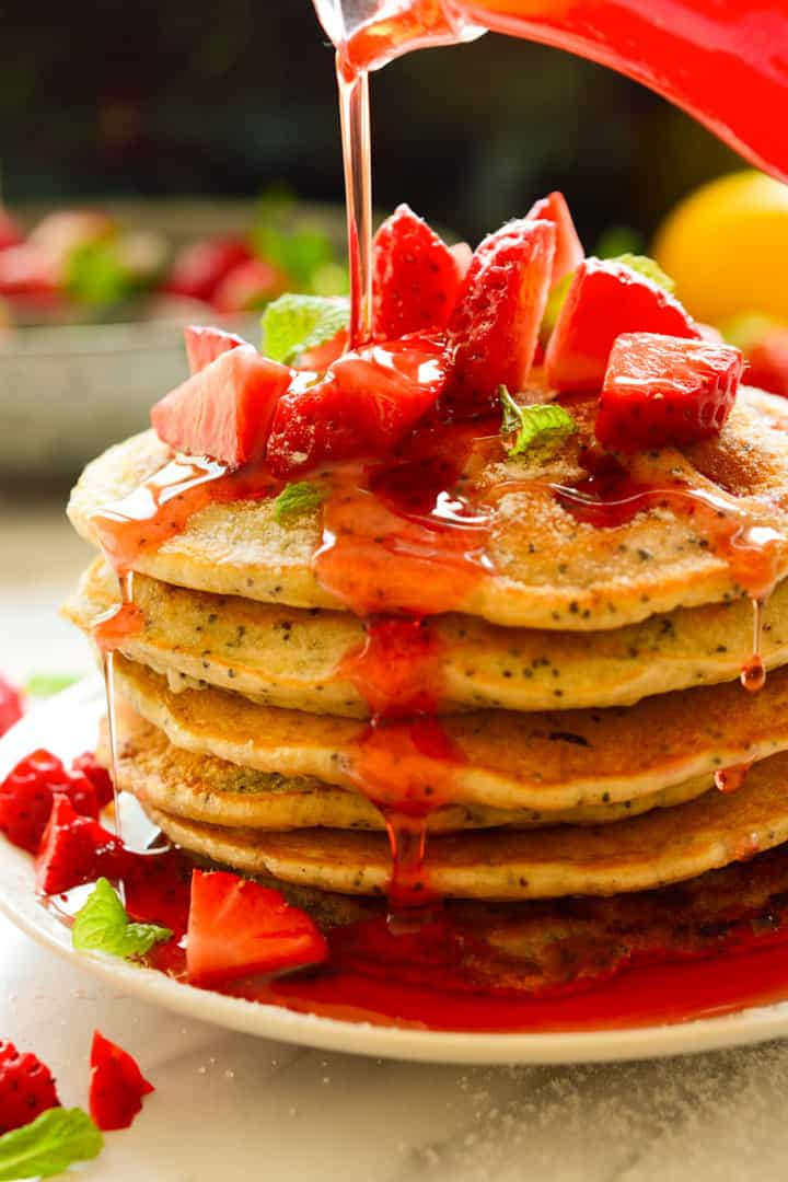 a stack of vegan pancakes on a red plate with strawberries on top and strawberry sauce being poured over the pancakes