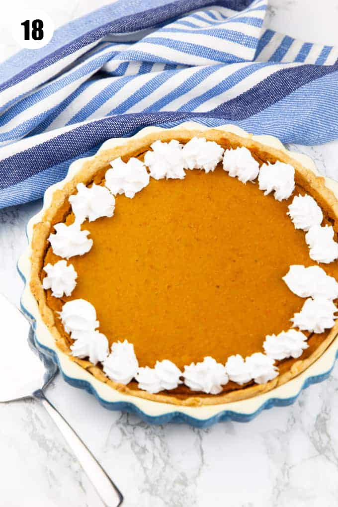 a vegan pumpkin pie decorated with coconut whipped cream on a marble countertop