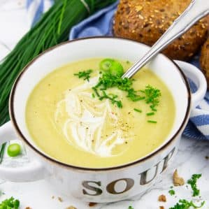 a bowl of cauliflower soup with chopped chives and green onions on top with a spoon on a marble countertop