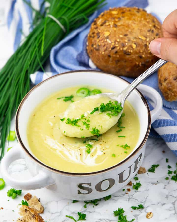 a bowl of cauliflower soup on a marble countertop with chives and a bun in the background and a hand holding a spoon
