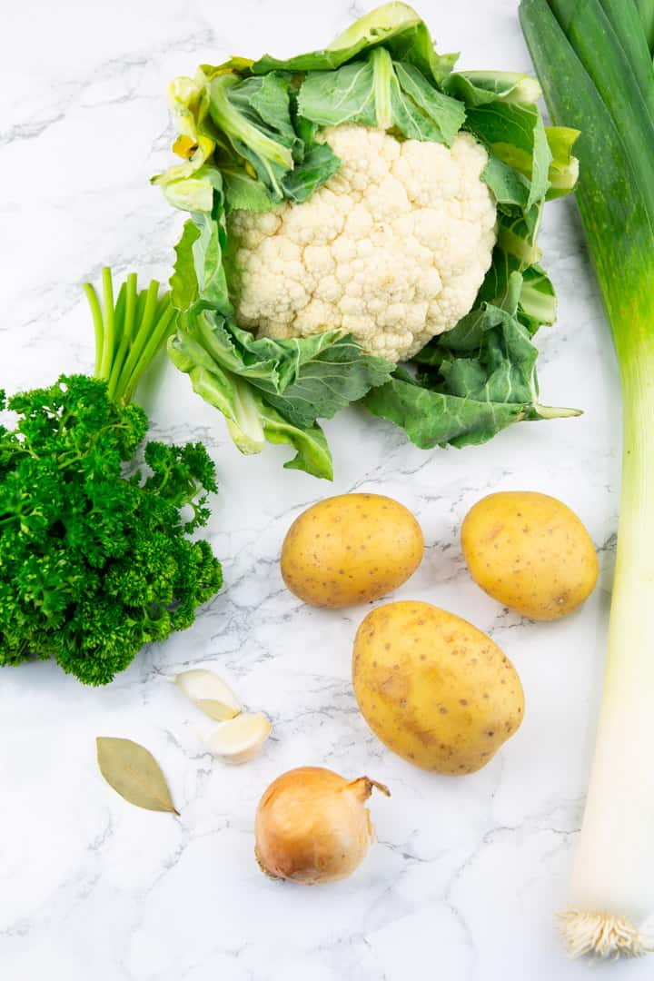 a cauliflower, three potatoes, an onion, a stalk of leek, and two cloves of garlic on a marble countertop
