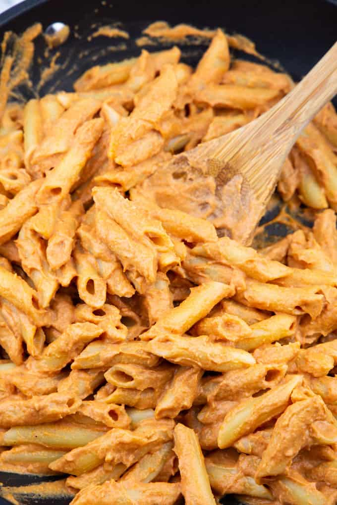 close-up photo of penne with vegan pasta sauce in a black pan with a wooden spoon