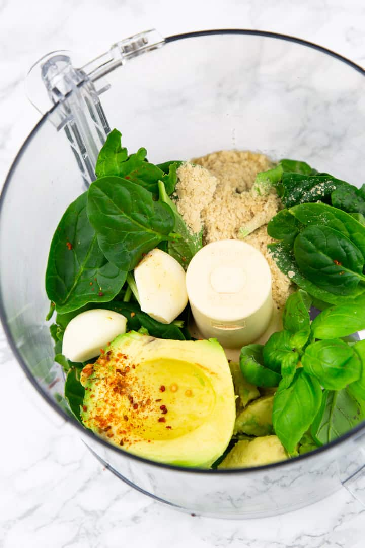 baby spinach, basil leaves, avocado, and garlic in a food processor on a marble countertop