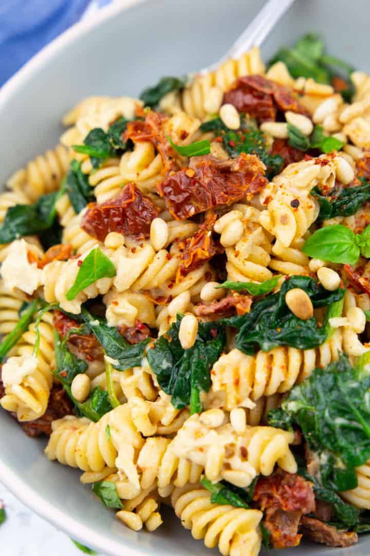 Hummus pasta with spinach, sun-dried tomatoes, and pine nuts in a light blue bowl with a fork