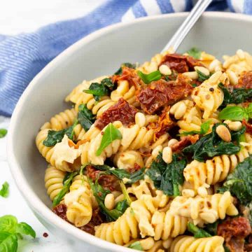 a bowl with rotini pasta with spinach, sun-dried tomatoes, and hummus on a marble countertop