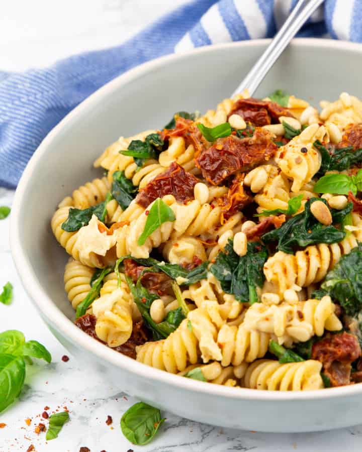 a bowl with rotini pasta, spinach, and sun-dried tomatoes on a marble countertop