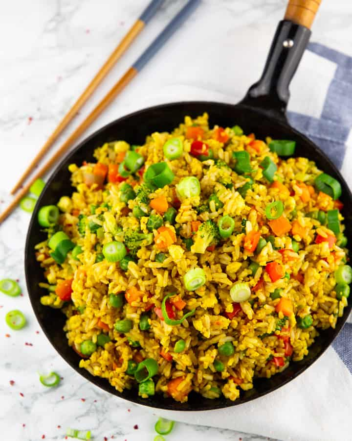 vegan fried rice in a black pan on a marble countertop with chopsticks in the background