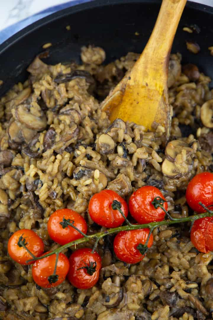 a close-up photo of mushroom risotto with roasted tomatoes in a black pan with a wooden spoon