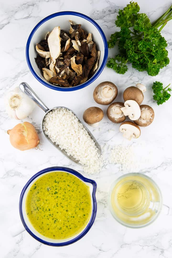 ingredients for mushroom risotto on a marble countertop (mushrooms, dried mushrooms in a bowl, rice, parsley, an onion, and garlic)