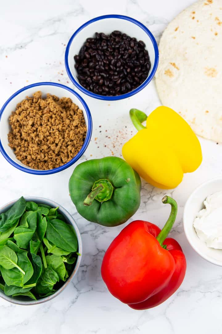a yellow, a green, and a red bell pepper on a marble countertop with three bowls with black beans, baby spinach, and veggie ground meat on the side