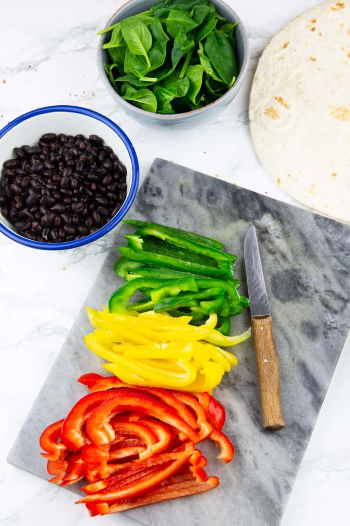 red, yellow, and green bell pepper slices on a marble cutting board with a knife and two bowls with baby spinach and black beans in the background