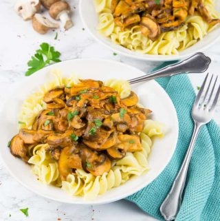 a white plate with mushroom stroganoff over pasta with a fork on a marble countertop with another plate in the background