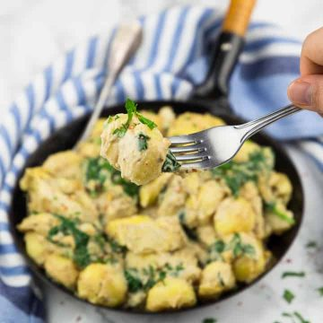 Spinach Artichoke Gnocchi in a black pan on a marble countertop with a hand picking up gnocchi with a fork