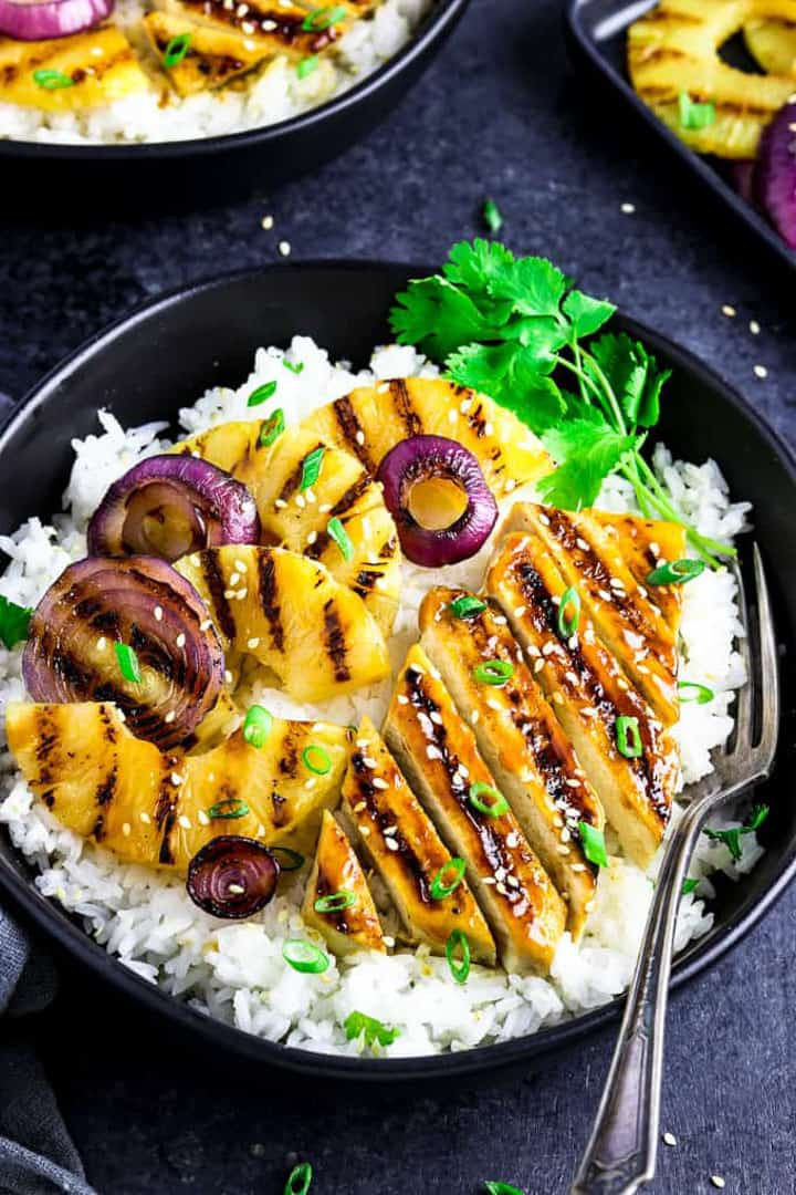 a Grilled Pineapple Teriyaki Bowl on a black countertop with a fork on the side