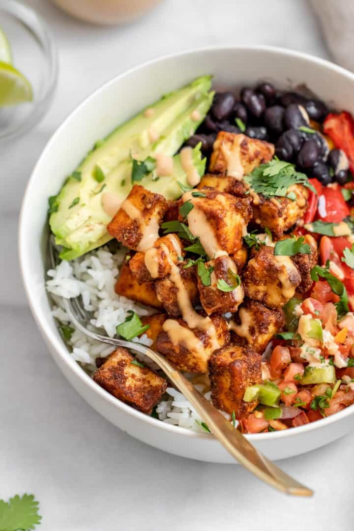 a bowl with rice, tempeh, black beans, and avocado on a white countertop