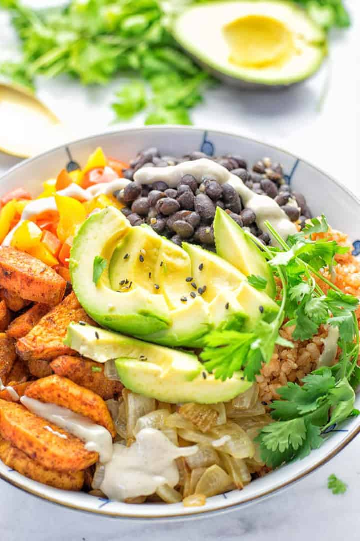 a white bowl with sweet potatoes, black beans, and avocado on a white countertop with an avocado and fresh cilantro in the background
