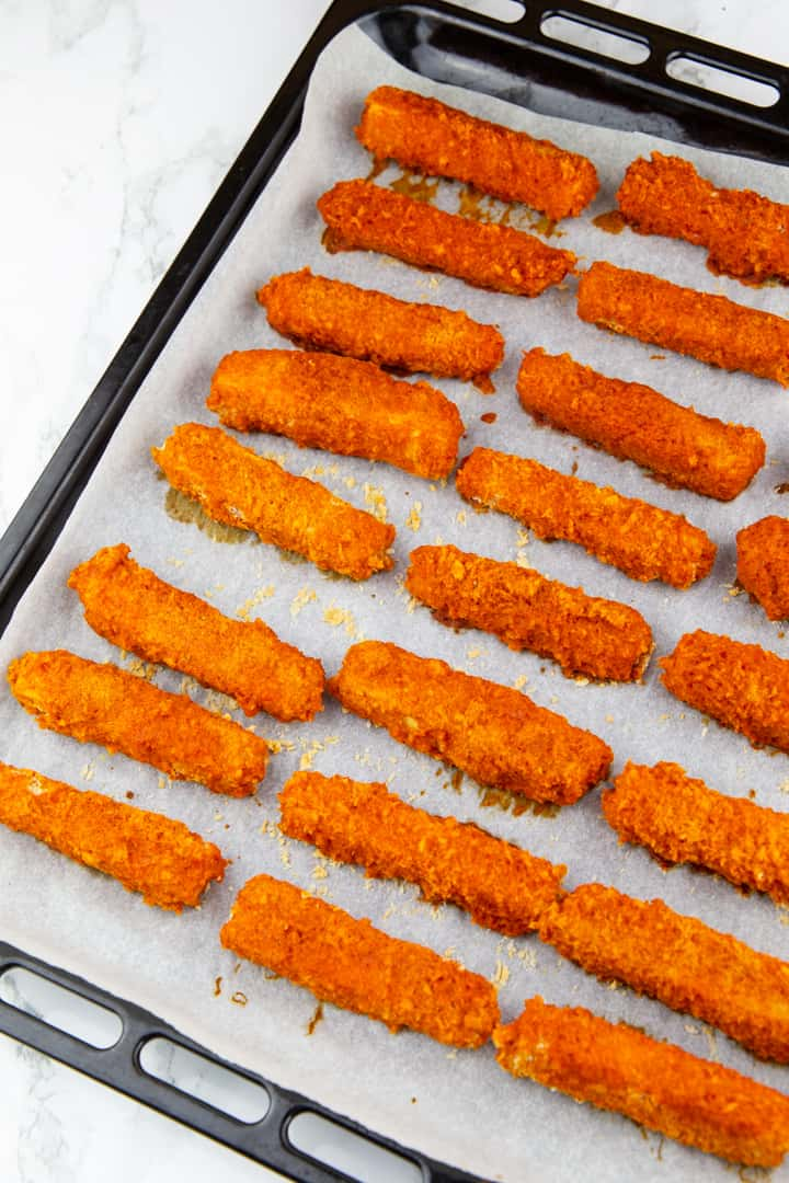 Baked Tofu Sticks covered in Frank's Red Hot sauce on a baking tray lined with parchment paper