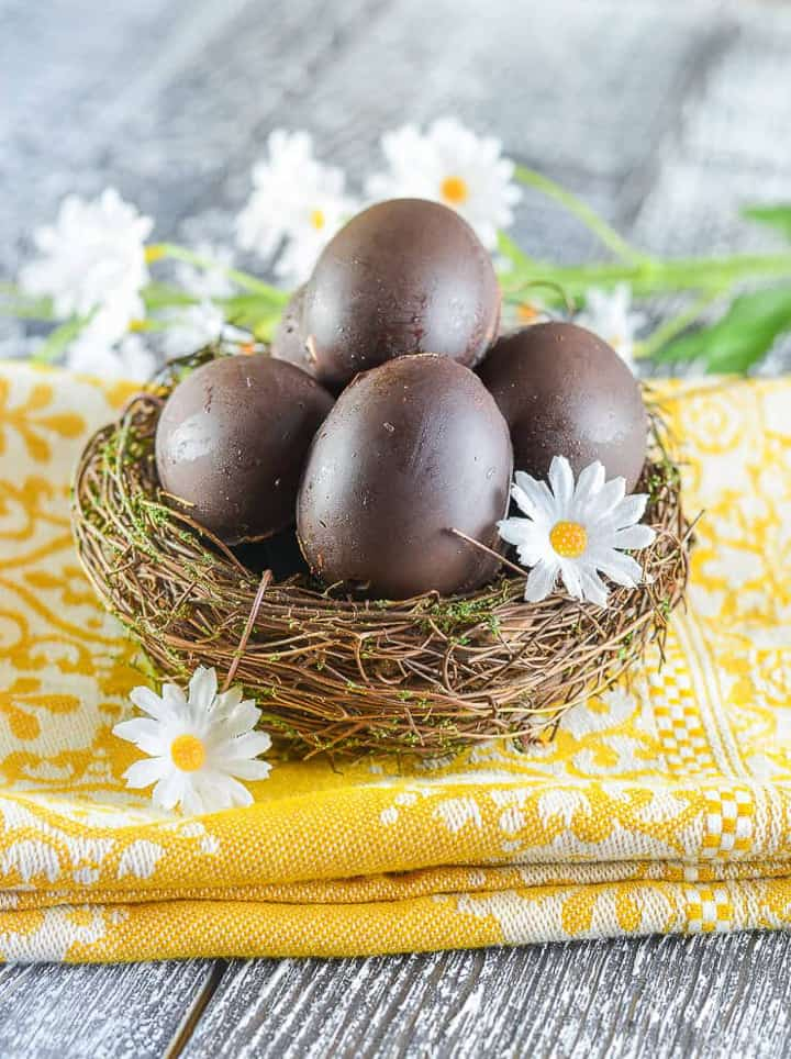 four vegan cream eggs in a basket on a yellow dish cloth