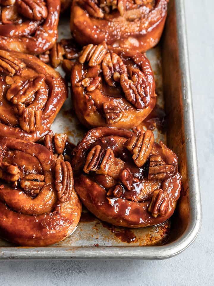 six vegan carrot cake sticky buns in a baking dish