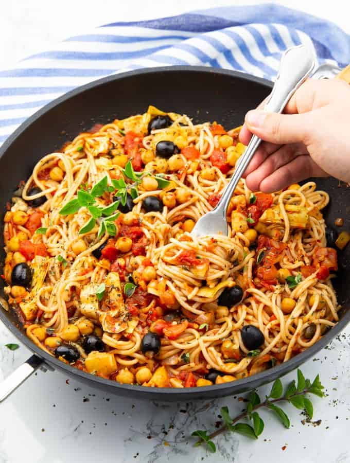 a pan with spaghetti with tomato sauce, chickpeas, and olives with a hand picking up some of the spaghetti with a fork