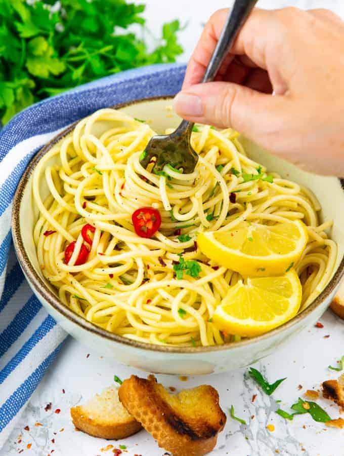 a bowl of spaghetti agile e olio with a hand holding a fork