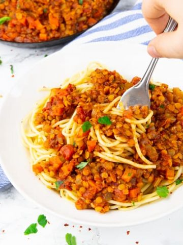 a white bowl of lentil bolognese with spaghetti with a hand holding a fork and a pan of bolognese sauce in the background