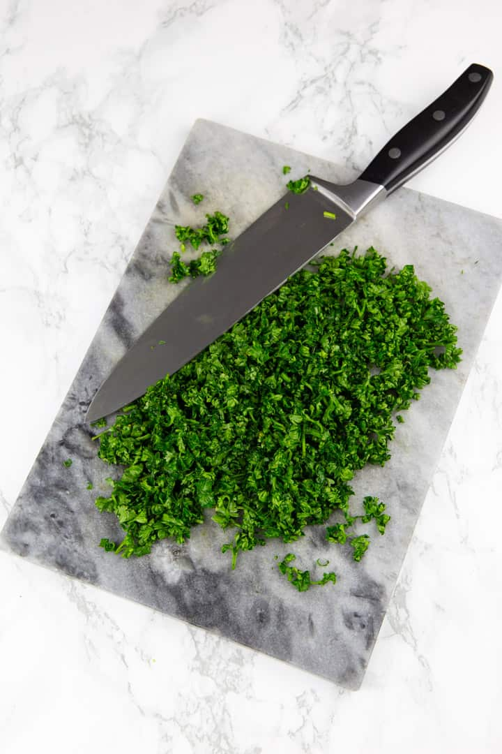 finely chopped parsley with a large kitchen knife on a marble cutting board