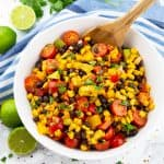a white bowl with Mexican salad with corn and black beans on a marble countertop with limes and cilantro in the background