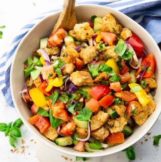 Panzanella in a white bowl on a marble countertop with basil leaves on the side