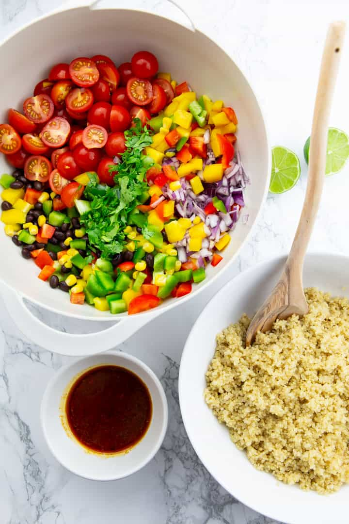 a bowl with cherry tomatoes, black beans, corn, and cilantro with a smaller bowl of quinoa and another small bowl with dressing on a marble countertop