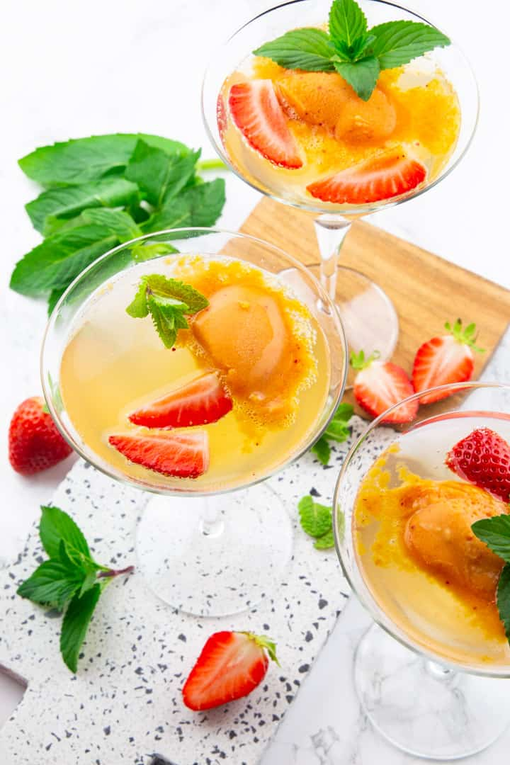 three glasses of champagne with strawberry sorbet, strawberries, and mint on a marble countertop