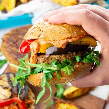 a hand holding a vegan burger with grilled vegetables and arugula with fries in the background