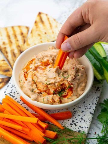 a hand dipping a carrot stick into a small bowl of jackfruit buffalo dip with cucumber and carrot sticks on the side