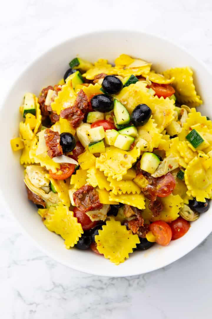 ravioli, black olives, and cherry tomatoes in a white bowl on a marble countertop