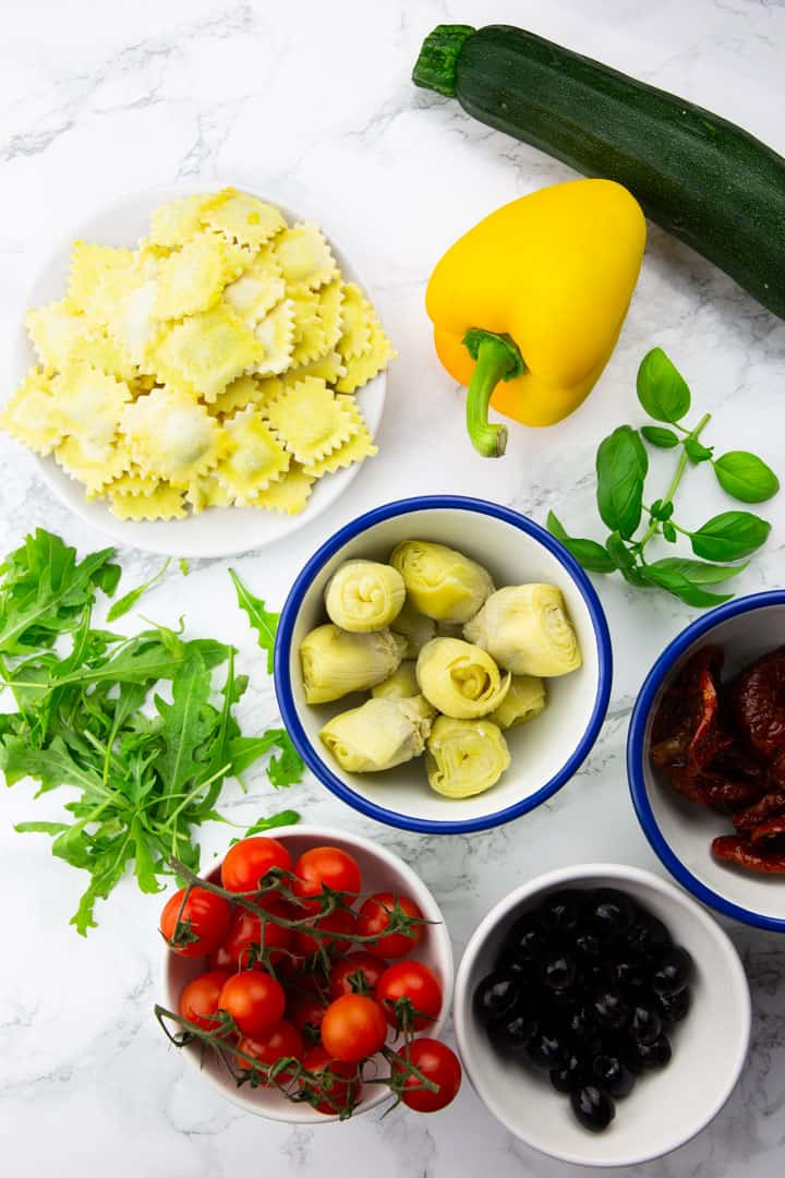 four small bowls with cherry tomatoes, artichoke hearts, olives, and sun-dried tomatoes as well as a yellow bell pepper a zucchini, arugula, basil, and a plate with ravioli on a marble countertop