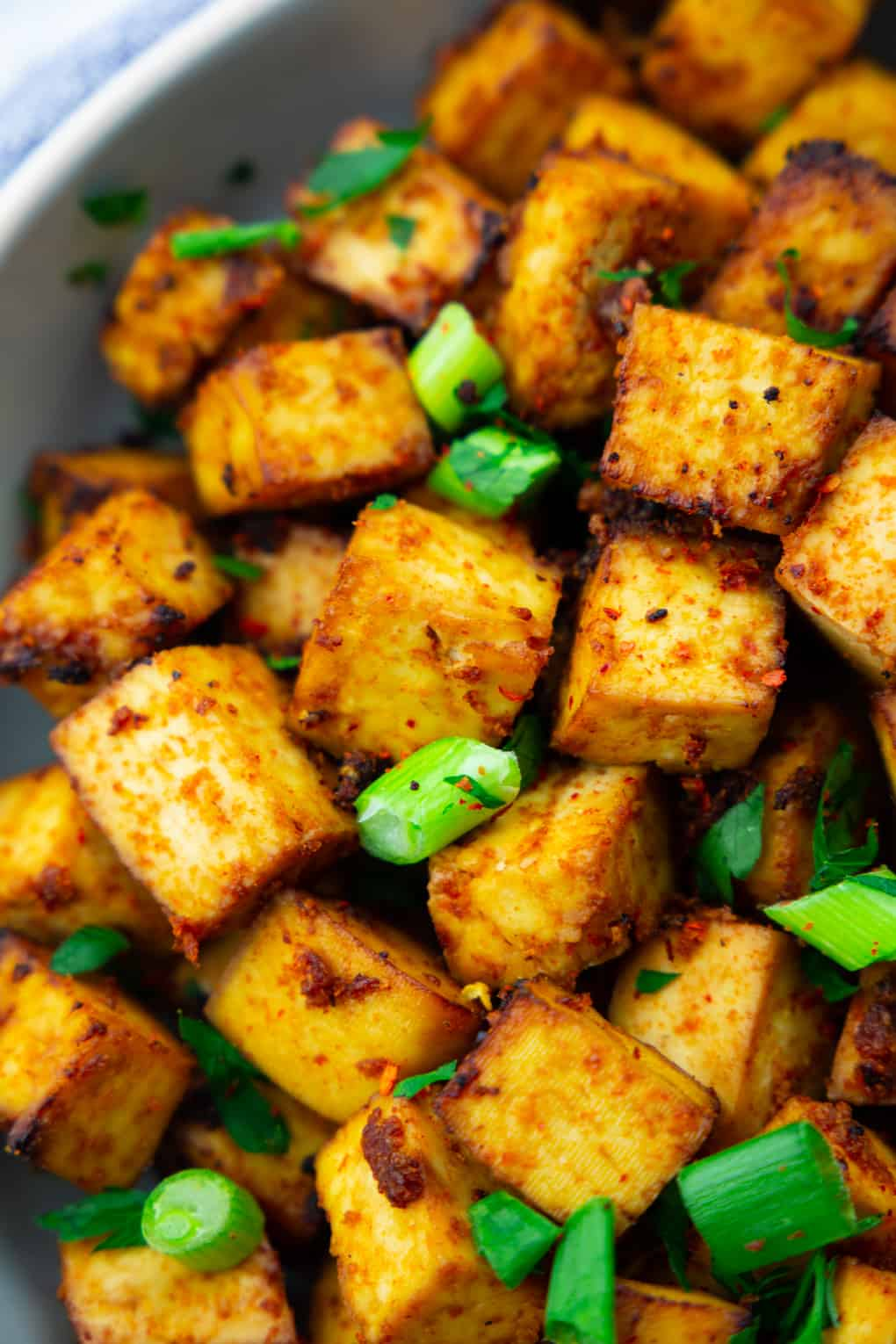 close-up photo of crispy tofu cubes with green onions sprinkled on top