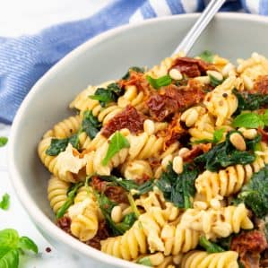 a bowl of hummus pasta with sun-dried tomatoes and spinach on a marble countertop